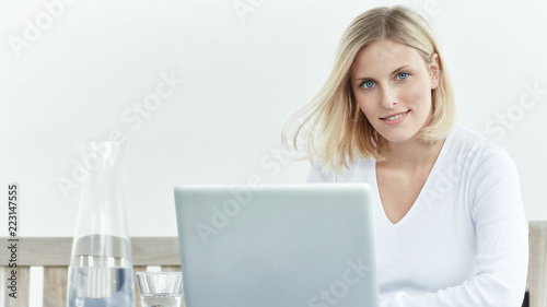 Frau im Homeoffice vor weissem Hintergrund - 223147555