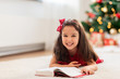 christmas, holidays and childhood concept - happy little girl lying on floor and reading book at home