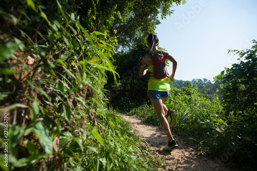Young fitness woman trail runner running in sunny forest