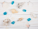 Collection of seashells and blue stones scattered on a white wooden background (top view) - 223173330
