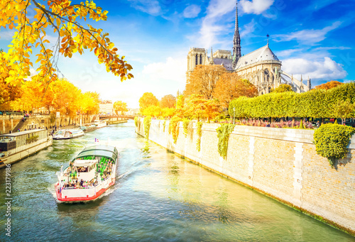 Leinwanddruck Bild Notre Dame cathedral over the Seine river with boat at fall, Paris, France