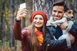 Woman and man with their dog on autumn walk taking a phone selfie posting it online on social media - 223181913