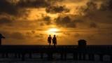 Couple on sunset background in Maldives.