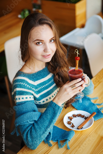 Naklejka Brown-haired woman drinking smoothie with cinnamon alone in cafe