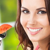 Smiling young woman eating tomato, outdoors - 223190373