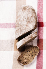 Freshly baked sliced rye bread on rustic tablecloth. Selective focus