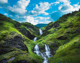 Waterfall, green hills and rolling clouds