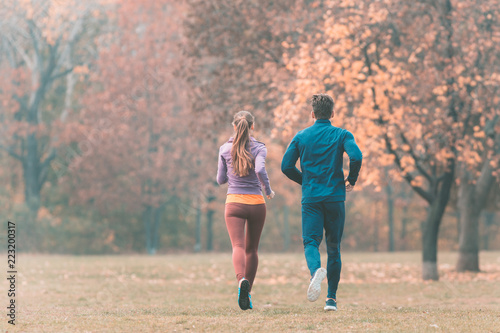 Leinwandbild Motiv Fall running in a park, seen from behind couple of man and woman