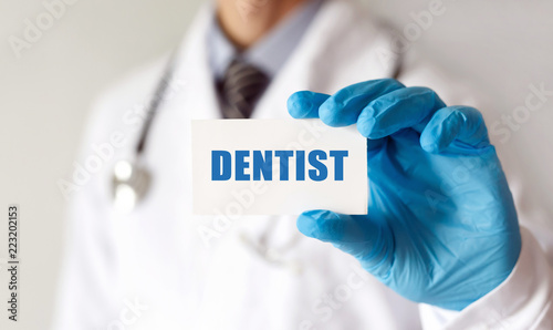 Fototapeta Doctor holding a card with text Dentist, Medical concept