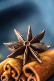 Star anise and cinnamon on a blue background, close-up. - 223207710