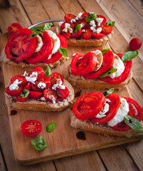 Bruschetta with cheese, tomatoes, fresh basil and balsamic vinegar on cutting board