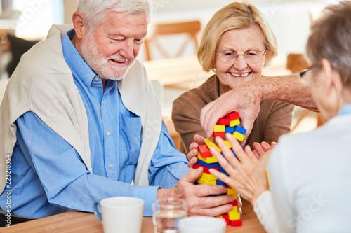 Leinwanddruck Bild Senioren Gruppe mit Demenz stapelt Bausteine