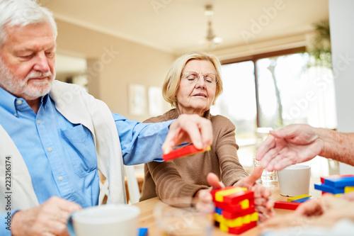 Leinwanddruck Bild Senioren mit Demenz stapeln Bausteine