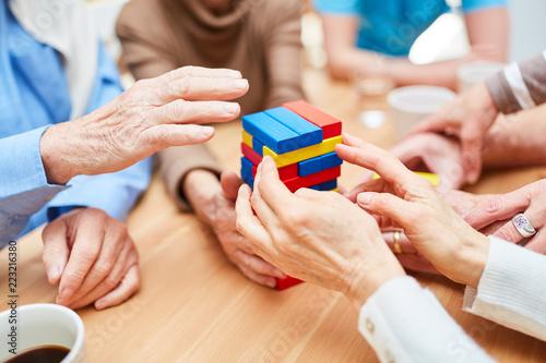 Leinwanddruck Bild Gruppe Senioren baut Turm aus Bausteinen