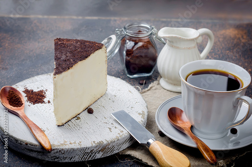cup of black coffee with a piece of soft cheese in ground coffee