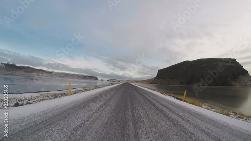 Middle road drive with blue sky and few clouds in Iceland Dyrholavegur between to frozen lakes and snow on the road.