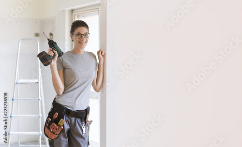 Foto Murales Professional repairwoman posing and holding a drill
