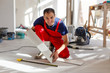 Leinwandbild Motiv Master is wearing work clothes, is checking horizon of installing tiles, using building level, adjusting, professional repairing work