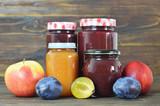 Fruit jam jars on wooden background