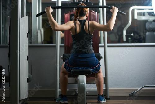 Potomstwa dostosowywali kobiety napina mięśnie na gym maszynie przed lustrem. Sport, fitness, trening siłowy