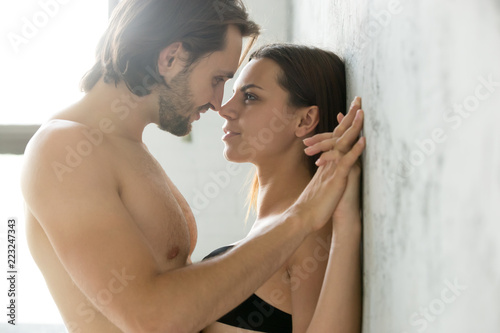 Leinwanddruck Bild Sensual couple holding hands looking in the eyes leaning on wall, passionate lovers enjoy tender romantic moment in bedroom, man get closer admiring girlfriend almost kissing having sex foreplay