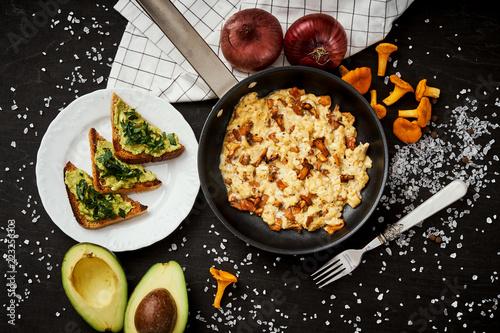 pyszne jajecznica z kurkami prosto z lasu na patelni i chlebem z awokado na drewnianym stole kuchennym