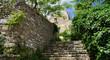 Leinwanddruck Bild - Treppe neben Steinmauer zu einem Haus aus Stein