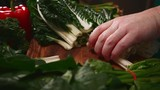 Woman's hands cut silverbeet spinach leaves on wooden cutting board in kitchen preparing healthy food - 223264556