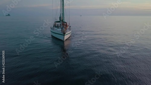 Panoramic drone shot of a sailing boat moving during the sunset in open water sea.