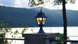 beautiful iron lantern with colored glass shines in the evening Park on the waterfront near the sea - 223299119