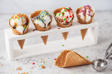 ice cream in cone with confectionery powder on stand over white background