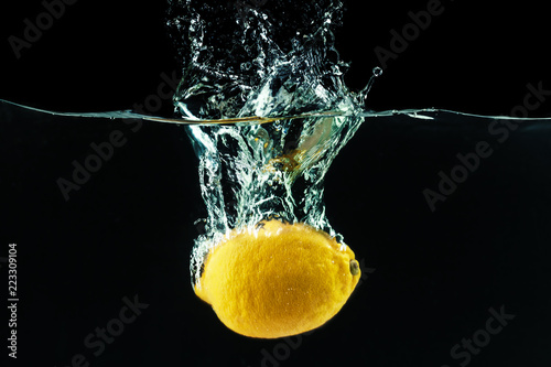 fresh yellow lemon in water splash on black background - 223309104