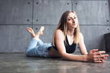 young beautiful woman professional dancer lies on the floor after workout rehearsal in dance fitness studio - 223327722