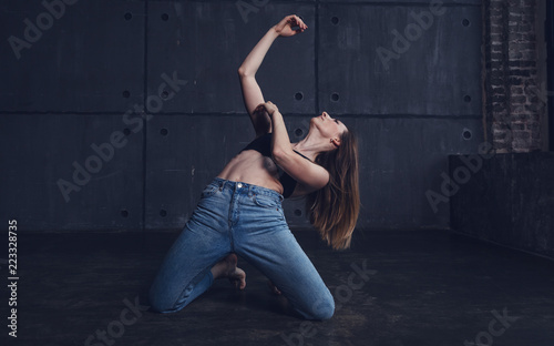 young beautiful woman in top and jeans dancing modern contemporary dance in the studio, contemporary art, harmony of body and soul, professional dancer - 223328735