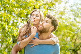 Woman and man on a meadow in romantic mood enjoying themselves and their life