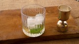 Measuring a shot of alcohol and pouring into a lowball glass with ice. - 223334766