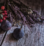 Ripe figs, berries and a heather on the old wooden background. Dark photo in vintage style. Autumn season.  - 223347352