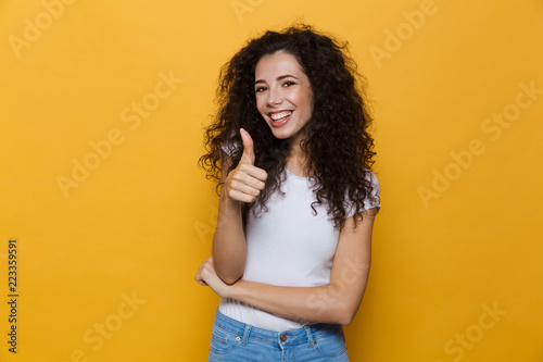 Image of young woman 20s with curly hair smiling and showing thumb up, isolated over yellow background