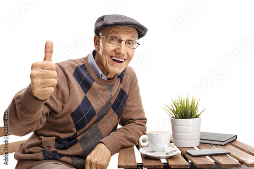 Senior sitting at a coffee table making a thumb up gesture