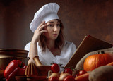 Young beautiful girl in a chef's uniform reads an old cookbook. - 223374120