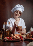 Young beautiful girl in a chef uniform with wooden mortar. - 223374356