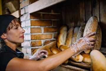 Female Shop Assistant Arrange Breads In Bakery Shop