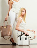 Two women in white clothes with bags handbags. - 223379311