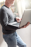 Senior businessman standing and working on his laptop - 223380971