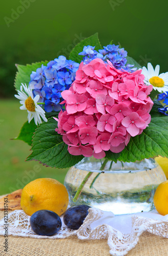 Colorful flowers bouquet in glass vase and fresh mixed fruits .