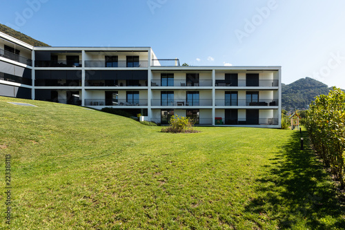 Exterior modern white condominium building with lots of lawn, - 223388113