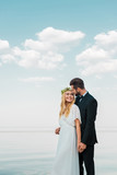 wedding couple in suit and white dress holding hands and looking at each other on beach - 223388335