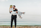 handsome groom in suit holding attractive bride in white dress on beach - 223388746