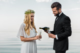 handsome groom pouring champagne into glasses on beach - 223389124