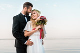 groom hugging smiling bride and she holding wedding bouquet on beach - 223390192